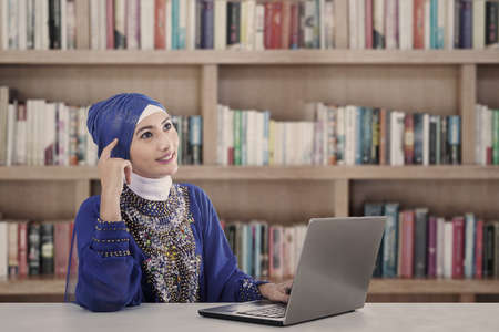 Asian female muslim thinking at library in blue dress photo