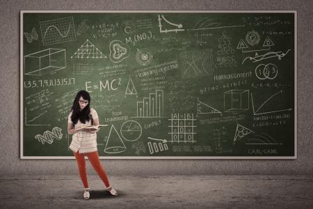 Asian female student is standing on written blackboard photo