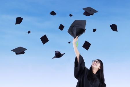 academic achievement: Asian graduate throw graduation cap under blue sky