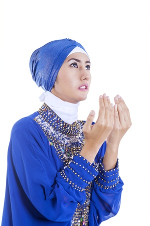 Beautiful muslim girl praying on white background photo