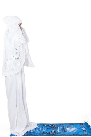 mujeres orando: Mujer musulmán asiática que ruega en la alfombra, aislado en blanco