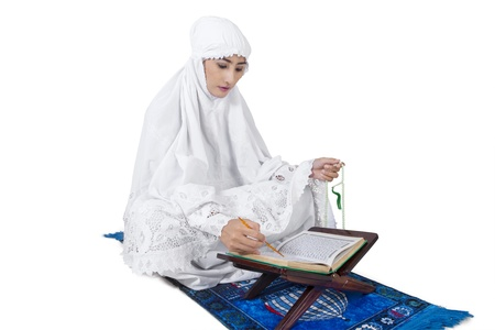 kur'an: Beautiful female muslim read Kuran on white background Stock Photo