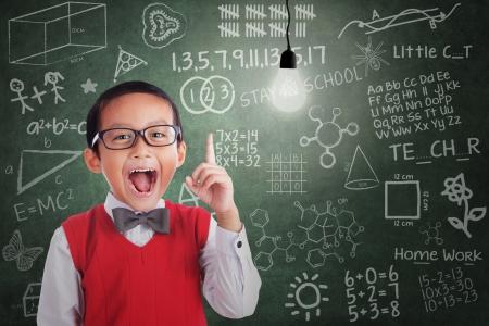 Asian student boy has idea under lit bulb in class with written board photo