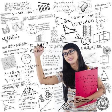 asian teacher: Asian female student is writing formula on whiteboard holding red folder