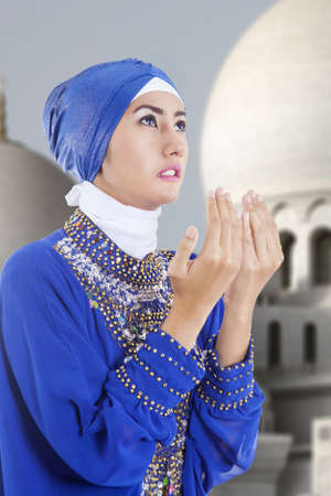 religious clothing: Beautiful muslim girl in blue praying at mosque Stock Photo