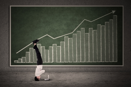 Businessman acrobatic move on profit bar chart while looking at a laptop Stock Photo - 20067435