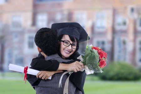 Happy student hugging boyfriend on graduation at school with flower bouquet photo