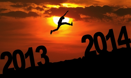 january sunrise: Silhouette of a man jumping from 2013 towards 2014 year at sunset