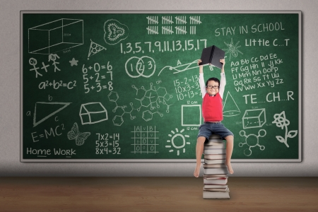 preschool classroom: Asian boy lifting a book while sitting on stack of books in classroom Stock Photo