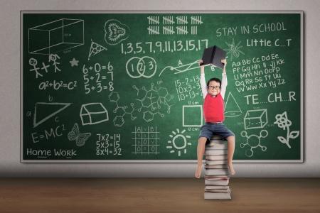 estudiando: Muchacho asiático que levanta un libro mientras está sentado en la pila de libros en el aula Foto de archivo