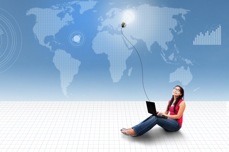 Asian female student using laptop looking at lightbulb on world map background photo