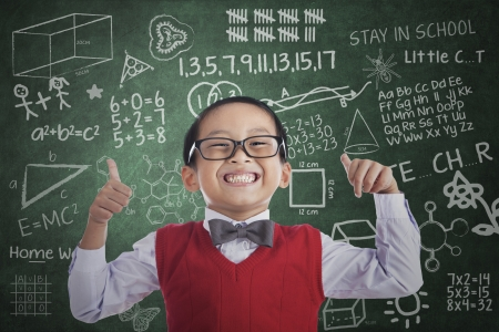 preschool classroom: Portrait of successful elementary school student showing his thumbs up in classroom Stock Photo