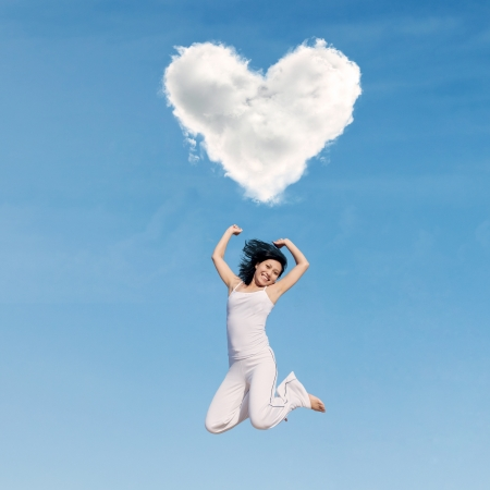 under heart: Asian woman jumping happily under heart cloud Stock Photo