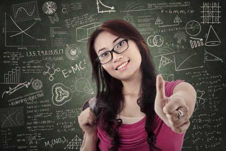 Attractive Asian female student shows thumb up in classroom photo