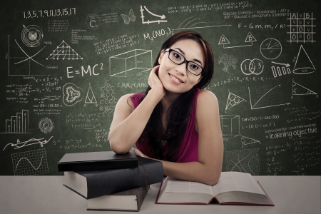 Smiling friendly female college student with textbooks in classroom Stock Photo - 20049424