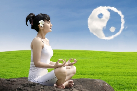 Attractive girl meditate yoga under ying yang cloud on the rock outdoor photo