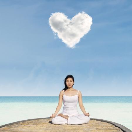 Asian woman meditating at beach under love cloud. Shot at tropical beach Stock Photo - 20048931