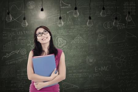 asian teacher: Beautiful female student looking at light bulbs in class Stock Photo