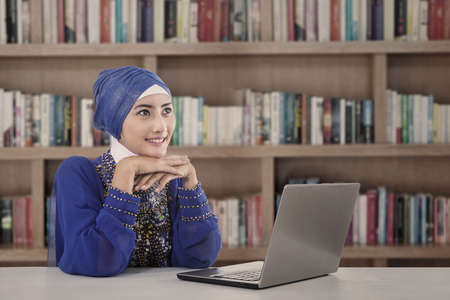 Beautiful female muslim study at library with her laptop Stock Photo - 20049416
