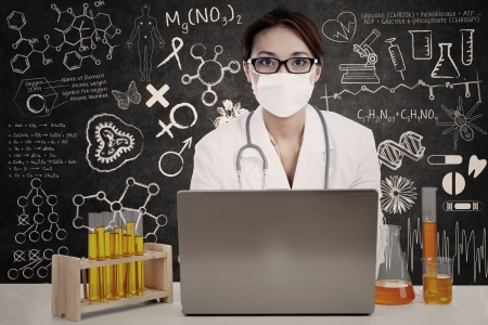 female scientist: Portrait of female scientist wearing mask with laptop computer and liquid chemical in test tube