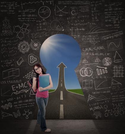 llave de sol: Bella estudiante de pie en el aula con el camino hacia el éxito a través de ojo de la cerradura Foto de archivo
