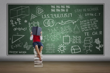 assignments: Boy reading book in class sitting on stack of books with written chalkboard