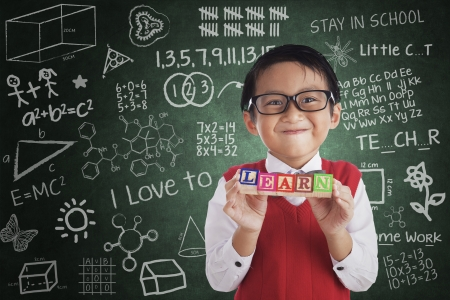indonesian: Boy smiling and holding LEARN crossword in class Stock Photo