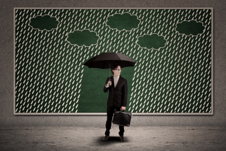 Businessman with umbrella under the rain on blackboard photo