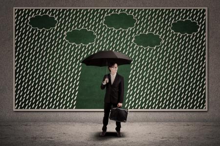 Businessman with umbrella under the rain on blackboard