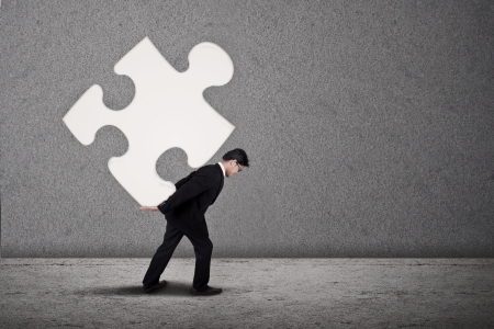 puzzles: Businessman in suit is building a puzzle on grey background