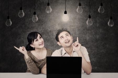 couple lit: Los estudiantes asi�ticos con port�til mirando la bombilla en la pizarra