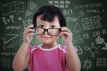Cute asian girl holding glasses in classroom Stock Photo - 20049527