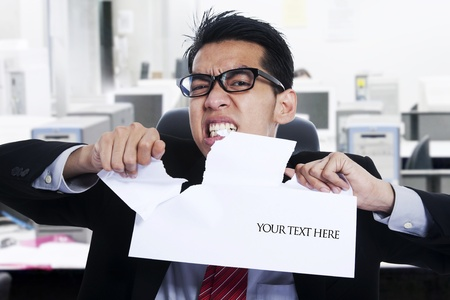 Angry Businessman ripping apart blank paper at the office photo