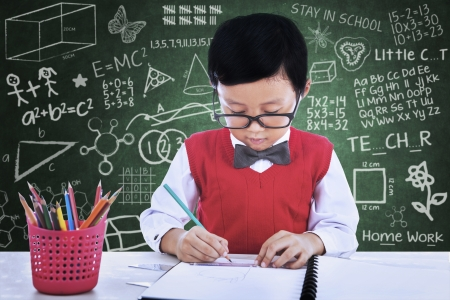 Asian student boy is drawing something on paper in class photo
