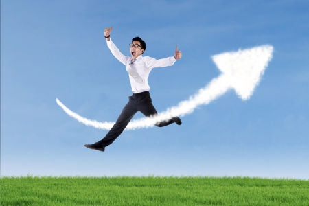 upturn: Asian businessman is jumping over up arrow sign cloud at the green field