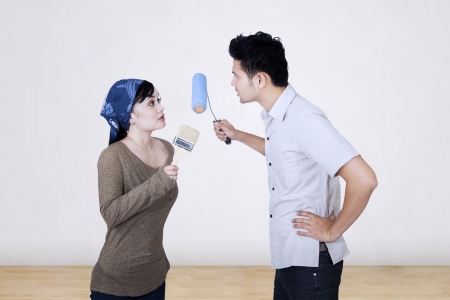 Asian couple is fighting over something while painting the wall photo