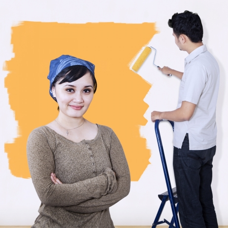 Girlfriend looking at camera while boyfriend painting wall in yellow photo