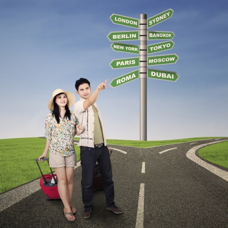 honeymoon couple: Asian couple pointing direction with road signs background, shot outdoor