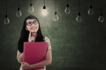 Asian female student looking at light bulbs in class Stock Photo - 20351016
