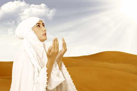 mujer rezando: Musulmán de Asia las mujeres con un vestido blanco que ruega en el desierto