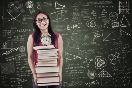 research study: Asian student is holding stack of books and clock in the classroom