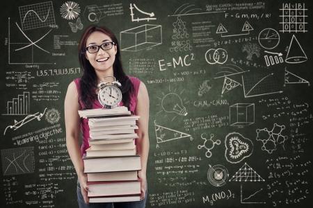 estudiar: Estudiante asiático está sosteniendo la pila de libros y el reloj en el aula
