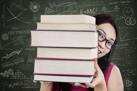 Close-up female student bring stack of books in classroom Stock Photo - 20352797