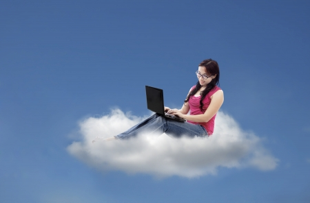 Attractive female student using laptop sitting on cloud photo