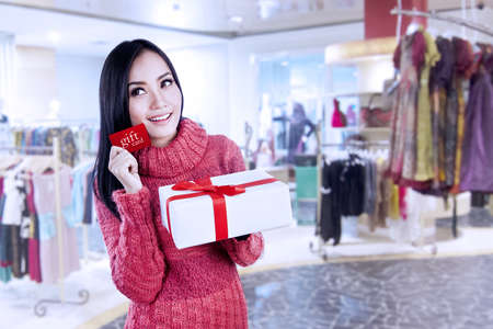 Asian woman show gift card and present in shopping mall photo