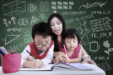 asian teacher: Beautiful teacher help children to write in classroom