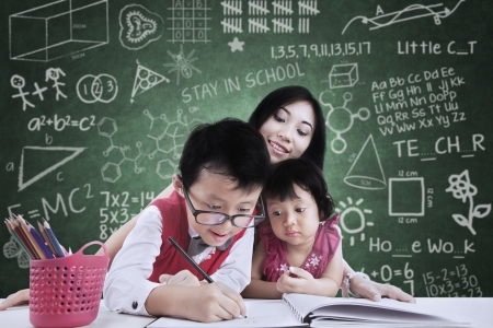 beautiful teacher: Asian sister and brother is learning to write in class with the teacher Stock Photo