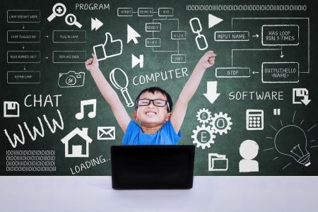 Gelukkig geek jongen winnen informatica concurrentie met behulp van laptop in de klas