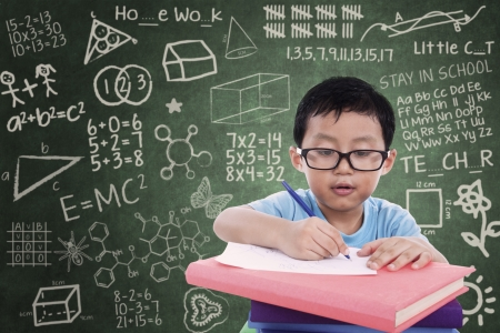 asian student: Young boy is writing on a book in classroom with written chalkboard