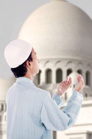 Asian muslim boy is praying at mosque photo